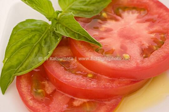 Sliced tomato and fresh basil leaves on a plate with olive oil