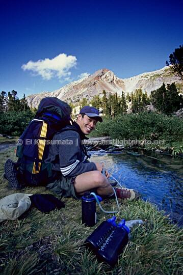 A backpacker filters water from a mountain stream near Duck Pass, John Muir Wilderness Area, California