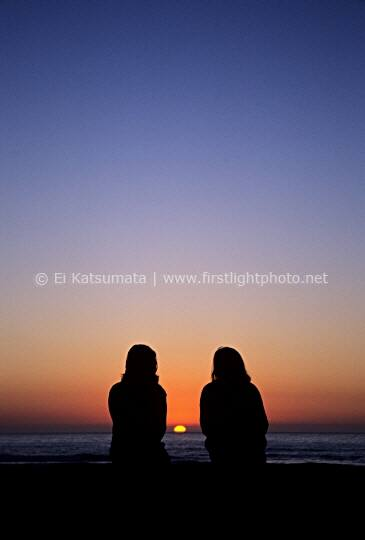 Two women enjoying the setting sun at Ocean Beach in San Francisco, California,  United States of America