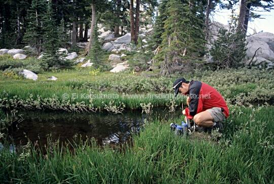 A hiker filters water from the headwaters of Squaw Creek in the Tahoe National Forest, California, United States of America