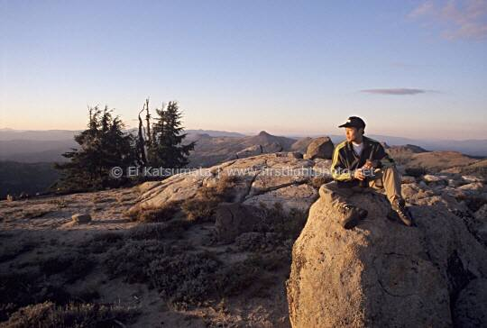 A hiker sitting on top of a boulder on the summit of Granite Chief peak in the Granite Chief Wilderness, Tahoe National Forest,  California, United States of America