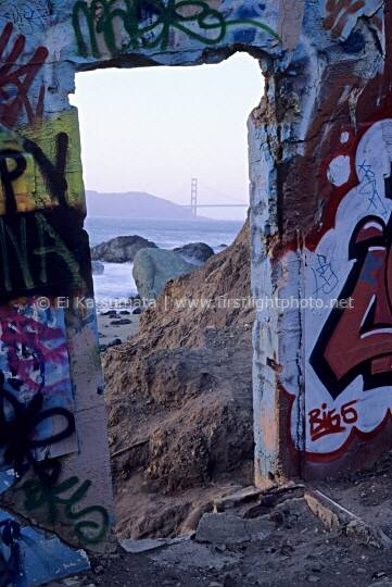 View of the Golden Gate Bridge through the doorway of a graffiti covered Army bunker in the Presidio of San Francisco, California