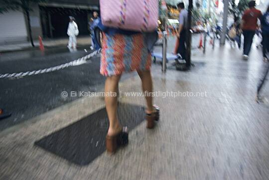 A fashionable woman walking the streets of Tokyo in the Shinjuku district after a light rain, Tokyo, Japan, Asia