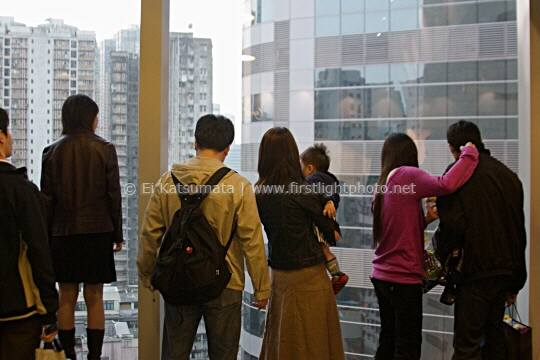 People looking out of a high-rise window, Mongkok, Kowloon, Hong Kong, China, Asia