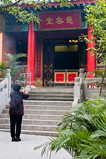 A woman offers incense as she prays at Sik Sik Yuen Wong Tai Sin Temple in Kowloon, Hong Kong, China, Asia