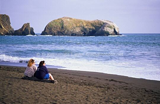 Two women sitting on a driftwood log at Rodeo Beach in the Golden Gate National Recreation Area in Marin County, California, United States of America