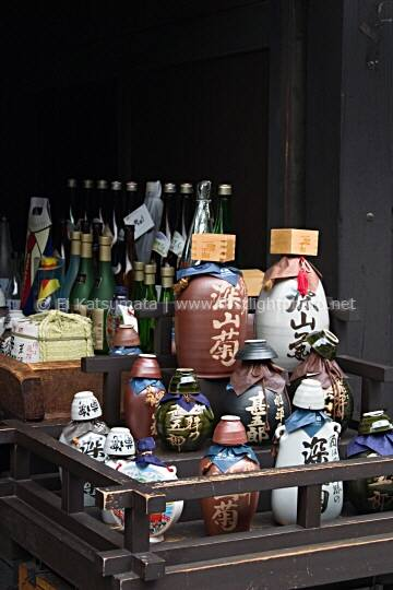 A variety of sake rice wine bottles on display in front of a sake brewery in Takayama, Gifu Prefecture, Japan