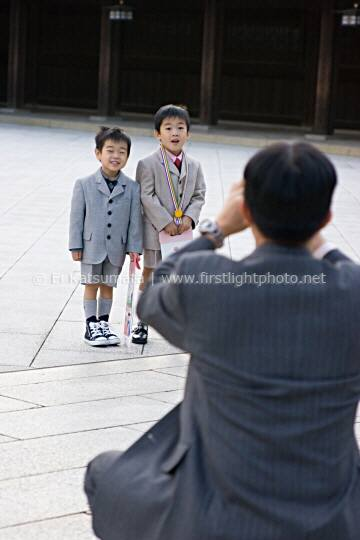 A man photographs two boys at Meiji-jingu shrine in Tokyo, Japan, Asia