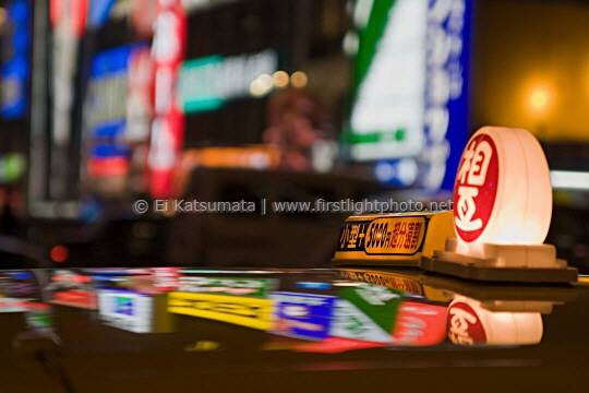 A taxicab reflects the bright lights of the Dotonbori district in Osaka, Japan