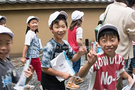 School children on a class outing waving at the camera, Kinkakuji Temple, the Golden Pavilion, Kyoto, Japan