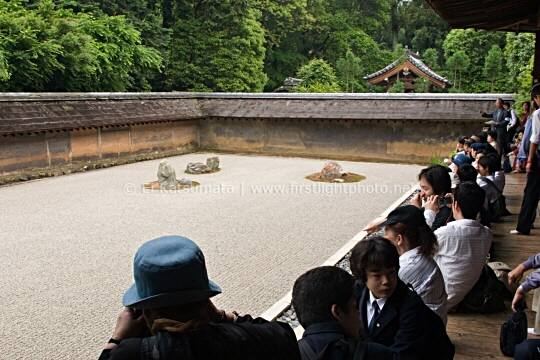 Visitors enjoy the view of the famous zen rock garden at Ryoanji Temple, Kyoto, Kansai Region, Japan