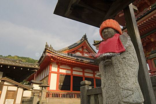 Jizo statue wearing an orange hat and bib at Kiyomizu-dera Temple, Kyoto, Kansai Region, Japan
