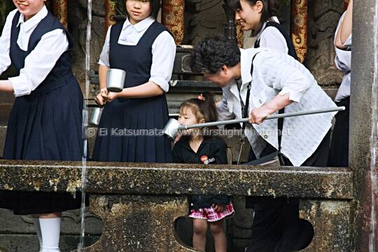A young girl drinking spring water from Otowa-no-taki at Kiyomizu-dera Temple, Kyoto, Kansai Region, Japan
